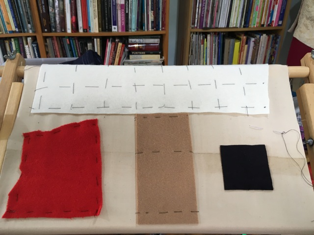 Four felt pieces tacked to backing fabric on frame