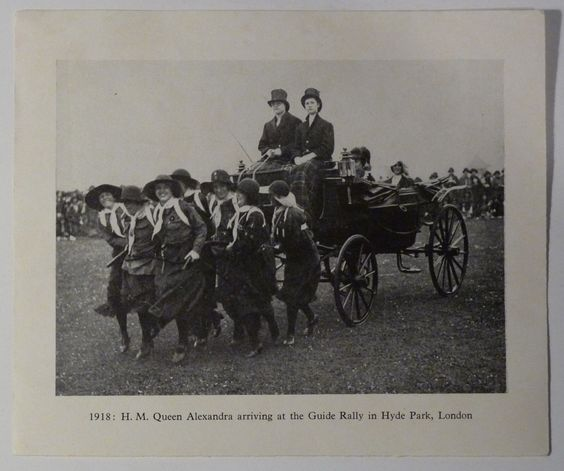 Girl Guide uniform showing rucksacck, and girls pulling Queen Alexandra, 1918.
