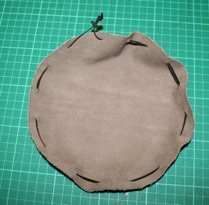 Thread leather thong through slits cut in circle to create your simple pouch. Finish on the outside.