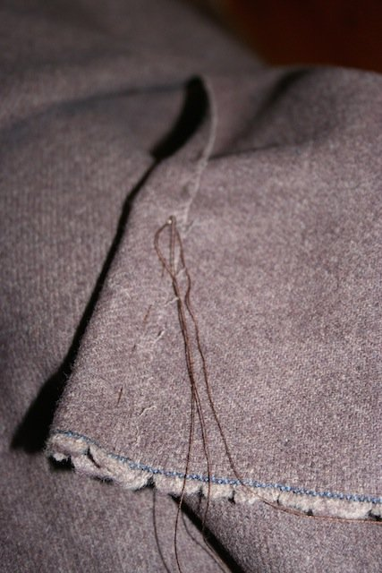 Tacking down the edge of a viking cloak before covering it with tablet-woven braid.