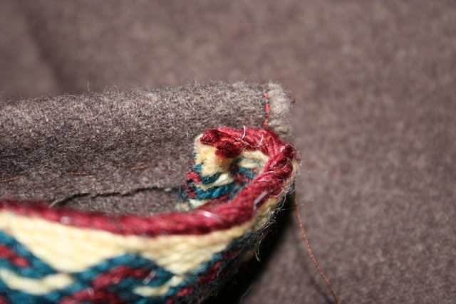 Turn the ends of the braid under and stitch down firmly before you cover the raw edge of the fabric with braid.